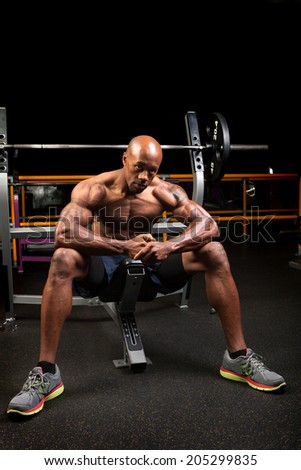 Weight lifter sitting at the bench press about to lift a barbell. - stock photo