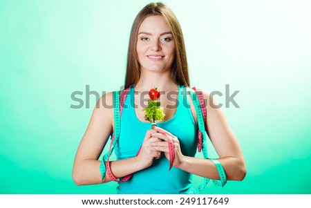 Weight loss and dieting concept. Sporty girl fitness woman holding fork with vegetarian food on blue green background in studio.