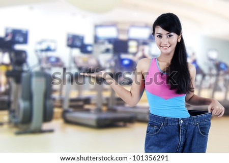 Weight loss concept: Beautiful Asian woman showing her old jeans, shot in fitness center