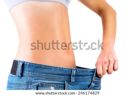 Weight loss concept.Close up of a woman's waist inside blue jeans. - stock photo