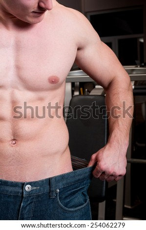 Weight loss concept with a fit man wearing larger pants or jeans - stock photo