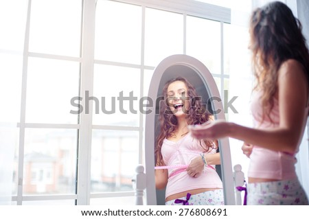 Weight loss. Happy young woman measuring her waist while looking at mirror at home. - stock photo