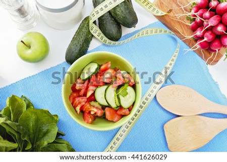 Weight loss, healthy diet and the concept of vegetarian food. Green ceramic bowl of delicious salad of cucumbers and tomatoes and vegetables on the kitchen table.