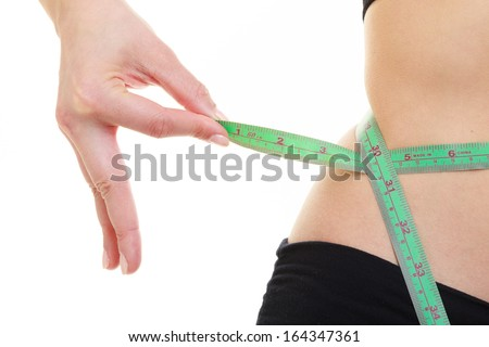 Weight loss, healthy lifestyle concept. Green measuring tape on woman body, fit girl measuring her waistline isolated on white background - stock photo