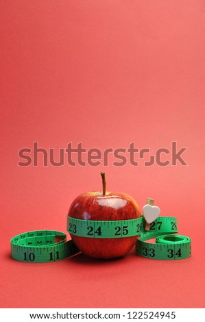 Weight loss slimming diet concept, New Year Resolution, with green measuring tape around a bright red apple, set against a red background. (vertical portrait orientation) - stock photo