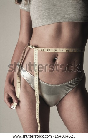 weight loss woman in bikini with tape measure