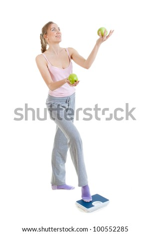Weight loss woman on scales juggles apples - stock photo