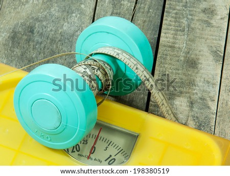 weight scale machines and measuring tape on the around  thousand dumbbells - stock photo