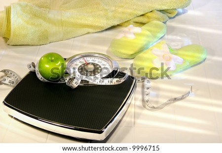 Weight scale on tile floor with towel and slippers/ Conceptual image for diet and - stock photo