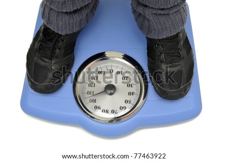 Weight scale with woman's feet isolated in white