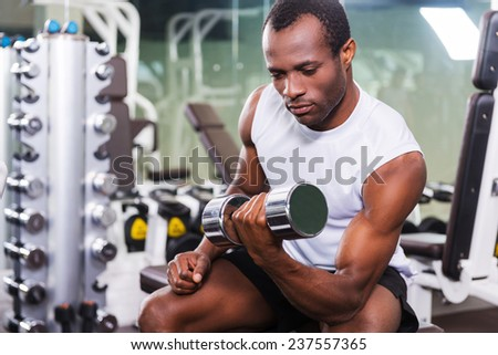 Weight training. Confident young African man training with dumbbell in gym - stock photo