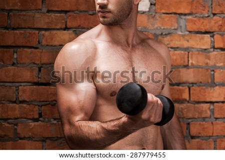 Weight training. Cropped image of young muscular man training with dumbbells while standing against brick wall