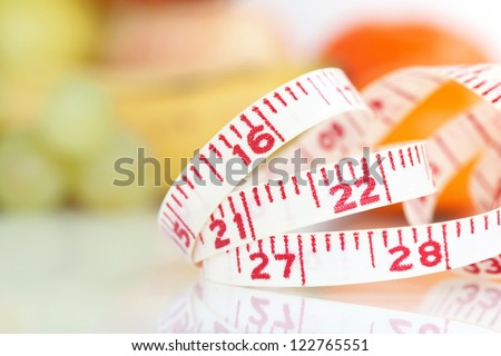 Weight watcher - Measuring tape with different fruits at the background (V-Format ID 174374312) - stock photo