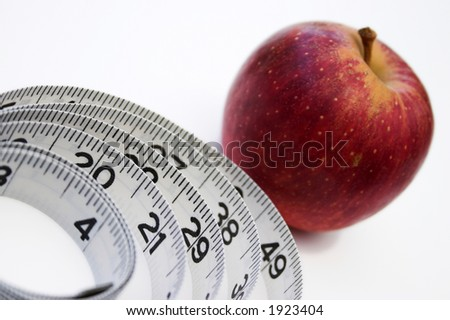 Weight watching concept, red apple & measuring tape on white - slight shadows