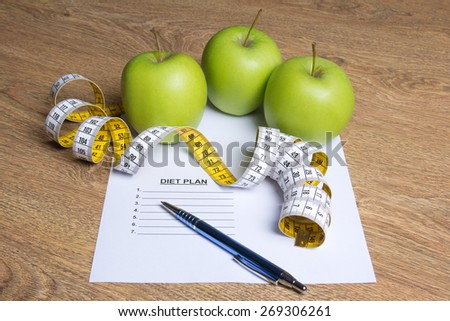weightloss concept - close up of paper with diet plan, apples and measure tape on wooden table - stock photo