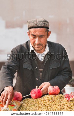 WEIHAI-NOV. 30, 2006. Muslim vendor sells grapes. When they settle in cities, many migrants become vendors. It requires small investment, but because of its informality, it is often sanctioned.   - stock photo