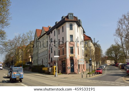 WEIMAR, GERMANY - APRIL 12, 2016. Street view on intersection of Friedrich-Elbert-Strasse and Eduard-Rosenthal-Strasse in Weimar, with residential building, commercial properties, people and cars.