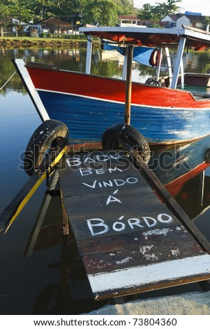 Welcome aboard message written in Portuguese on a gangplank leading to a wooden boat in Paraty, Brazil. - stock photo