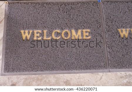 Welcome carpet on floor. - stock photo