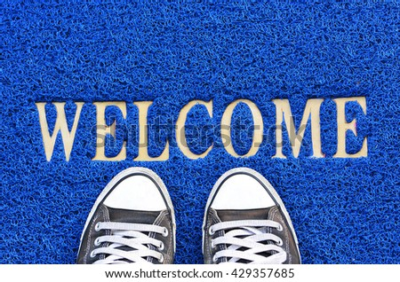 Welcome carpet with black shoes on it. - stock photo