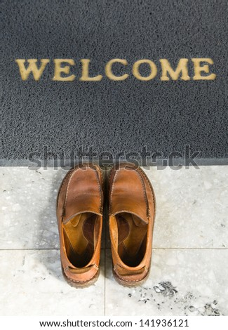 Welcome cleaning foot carpet with shoes - stock photo