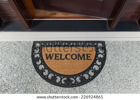 Welcome door mat with open door  - stock photo