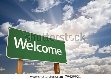 Welcome Green Road Sign Against Clouds and Sunburst. - stock photo