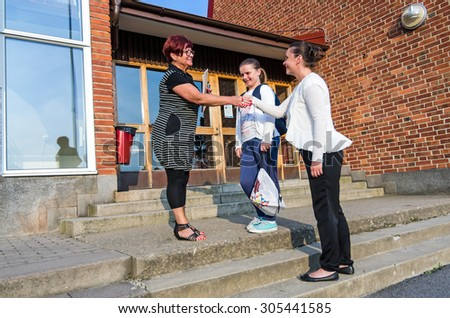 Welcome handshake between schoolgirl mother and teacher