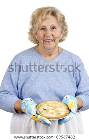 Welcome home concept: grandma is smiling while offering warm homecooked meat pie, wearing oven mitts. - stock photo