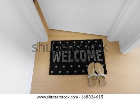 Welcome home doormat with open door - stock photo