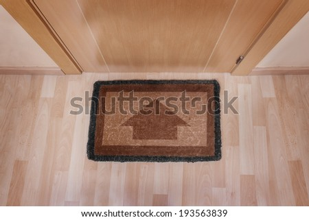 Welcome home on brown mat with arrow - stock photo