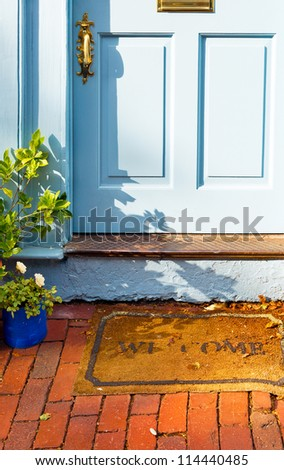 Welcome mat outside the front door of a vintage cottage - stock photo