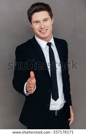 Welcome on board! Cheerful young man in formalwear stretching out hand for shaking while standing against grey background