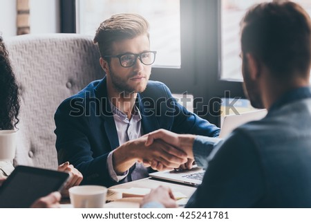 Welcome on board! Close up two men shaking hands and looking at each other while sitting at the business meeting  - stock photo