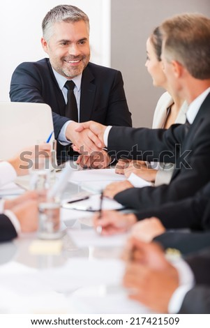 Welcome on board! Confident mature man in formalwear shaking hand to one of his colleagues and smiling while sitting at the table together  - stock photo
