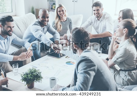 Welcome on board! Group of confident business people sitting around the desk together while two men shaking hands and smiling