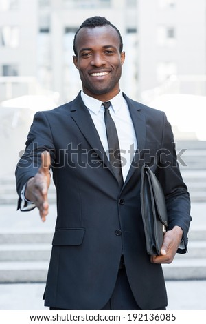Welcome on board! Handsome young African man in full suit stretching out hand for shaking while standing outdoors - stock photo