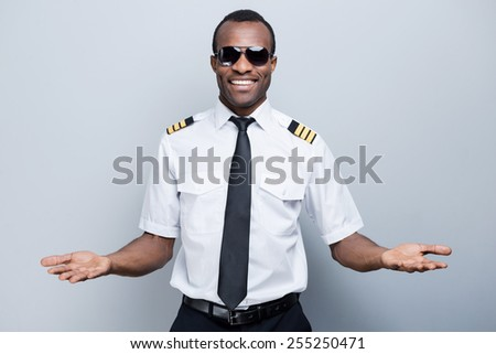 Welcome on board! Happy African pilot in uniform gesturing welcome sign and smiling while standing against grey background - stock photo