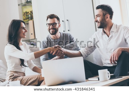 Welcome on board! Three young cheerful business people sitting together at the desk while man and woman shaking hands  - stock photo
