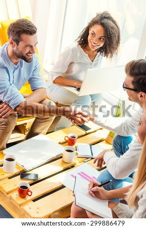Welcome on board! Two cheerful young men sitting at the wooden desk in office and shaking hands while two beautiful women looking at them and smiling  - stock photo
