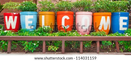 Welcome sign, at the flower pot. - stock photo