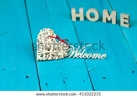 Welcome sign  attached to natural wicker heart with HOME blurred in background on antique rustic teal blue wood background; family and love concept - stock photo