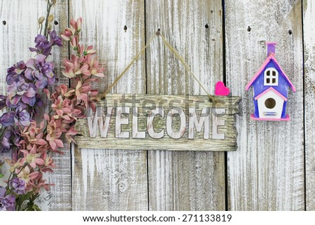 Welcome sign hanging on white fence by spring flowers and purple and pink birdhouse - stock photo