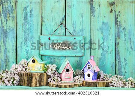 Welcome sign hanging over colorful birdhouses with butterfly on cedar logs by spring tree blossoms on antique rustic mint green wood background; pink, yellow, purple, green birdhouses - stock photo