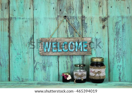 Welcome sign hanging over glass jars of fruit jelly on antique rustic mint green wood background
