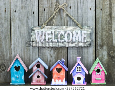 Welcome sign hanging over row of colorful pastel birdhouses with rustic wooden background - stock photo