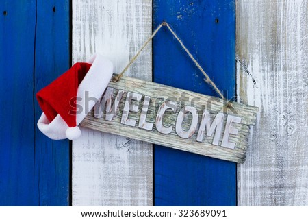 Welcome sign with red Santa Claus hat hanging on rustic blue and white fence - stock photo