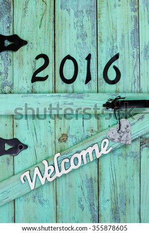 Welcome sign with year 2016 in black iron numbers and silver tin heart on antique rustic mint green wood door - stock photo