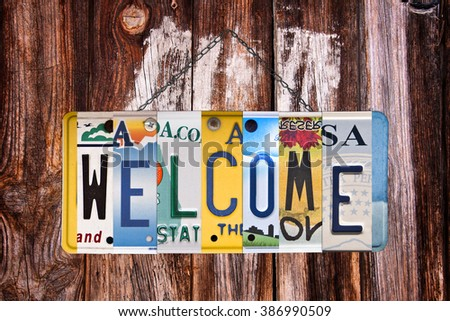 Welcome sign written with recycled US license plates - stock photo