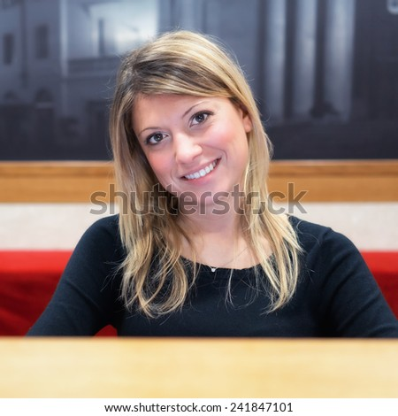 welcome, smiling girl on reception desk - stock photo